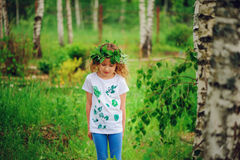 Child girl in summer forest. Idea for nature crafts with kids - leaf print shirt and natural wreath. Royalty Free Stock Image