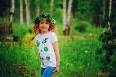 Child girl in summer forest. Idea for nature crafts with kids - leaf print shirt and natural wreath. Teaching kids to love nature royalty free stock photography
