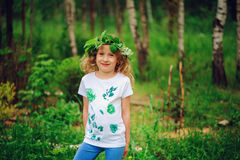 Child girl in summer forest. Idea for nature crafts with kids - leaf print shirt and natural wreath. Royalty Free Stock Images