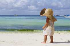 Child girl in summer hat on tropical sea background. Young child girl in summer hat on tropical sea background Stock Photography