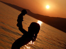 Child, girl in sunset with baby toys on sea Stock Photos