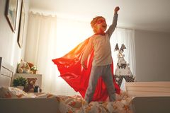 Child girl in a super hero costume with mask and red cloak royalty free stock image