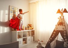 Child girl in a super hero costume with mask and red cloak. At home stock photo