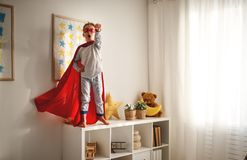 Child girl in a super hero costume with mask and red cloak. At home royalty free stock images