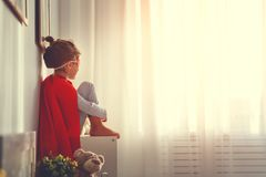Child girl in a super hero costume with mask and red cloak. At home stock image