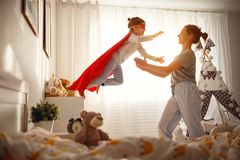 Child girl in a super hero costume with mask and red cloak. At home Royalty Free Stock Image
