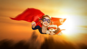 Child girl superhero with teddy bear flying through sky at sunse Stock Images