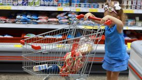Child girl in the supermarket buys food with trolley for products. Baby shopping. Child girl in the supermarket buys food with trolley for products. Baby stock video footage