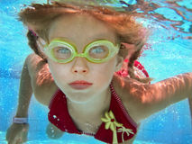 Child girl swim underwater in pool.