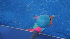 Small child girl is learning to swim in pool diving and floating in water. Child girl is swimming and diving underwater in pool. She is learning and training on stock footage