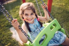 Child Girl Swinging At Playground Outdoors. In Summer stock images