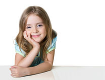 Child girl at the table isolated on white. Smiling girl. royalty free stock photography