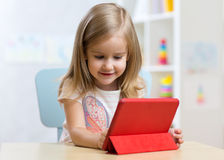 Child girl with tablet on floor at home Royalty Free Stock Images