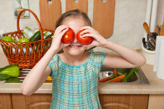 Child girl with tomatoes, vegetables and fresh fruits in kitchen interior, healthy food concept Royalty Free Stock Photography