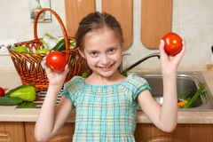 Child girl with tomatoes, vegetables and fresh fruits in kitchen interior, healthy food concept Stock Image