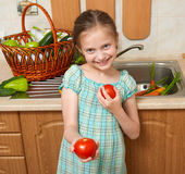 Child girl with tomatoes, vegetables and fresh fruits in kitchen interior, healthy food concept Stock Photography