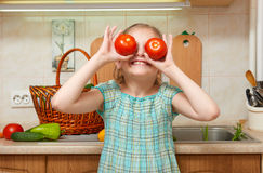 Child girl with tomatoes, vegetables and fresh fruits in kitchen interior, healthy food concept Royalty Free Stock Photos
