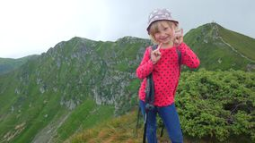 Child girl on top of the mountain. Shows rock fingers. stock video footage