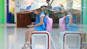 Child girl tourist in an airport terminal plays with a mobile phone. Baby uses a game application on a smartphone. Child girl tourist in an airport terminal stock footage