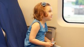 Child girl is traveling by train. Baby rides on a comfortable express train fast. Interest, curiosity, expectation stock footage