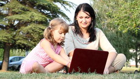 Child and girl typing on laptop Stock Photos