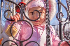 Child girl unusual portrait outdoor. Child girl looking through a forged fence outdoor Stock Images