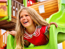 Child girl upside down on playground . Royalty Free Stock Photo