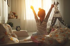 Child girl wakes up  and stretches in morning in bed and stretch Stock Photos