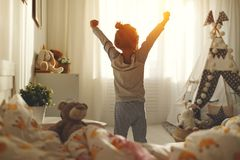 Child girl wakes up  and stretches in morning in bed and stretch Royalty Free Stock Image