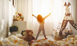 Child girl wakes up  and stretches in morning in bed and stretch. Child girl wakes up in morning in bed and stretches by window Stock Photography