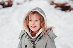 Child girl on the walk in winter snowy forest Stock Images