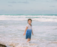 Child  girl walking in the Atlantic ocean near the beach on sunny warm day Royalty Free Stock Photography