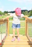 Child - girl walking on moving bridge. Small kid - little girl walking on moving bridge on kids playground Royalty Free Stock Photography