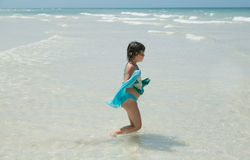 Child girl walking in the ocean on summer sunny gorgeous day Royalty Free Stock Photo