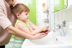 Child girl washing hands with soap in bathroom. Child girl and mother washing hands with soap in bathroom royalty free stock photos