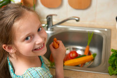 Child girl washing vegetables and fresh fruits in kitchen interior, healthy food concept Stock Images