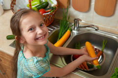 Child girl washing vegetables and fresh fruits in kitchen interior, healthy food concept Stock Photography