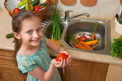 Child girl washing vegetables and fresh fruits in kitchen interior, healthy food concept Royalty Free Stock Image