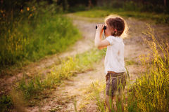 Child girl watching birds with binocular on the walk in summer forest Stock Photography
