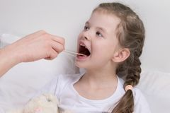 Child girl, watching the state of throat, wooden stick Royalty Free Stock Photos