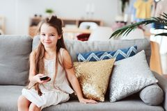 Child girl watching tv at home on cozy couch. Modern scandinavian interior, kids and television concept Royalty Free Stock Photography