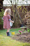 Child girl with watering can helps in spring garden Stock Photo