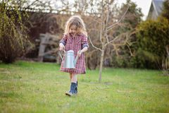 Child girl with watering can helps in spring garden Stock Images