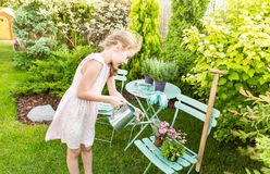 Child girl watering flowers outdoor in a summer garden Royalty Free Stock Photography