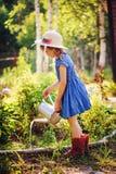Child girl watering flowers in summer garden, little helper Royalty Free Stock Photo