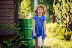 Child girl watering flowers in summer garden, little helper Stock Photos