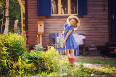 Child girl watering flowers in summer garden, little helper. Outdoor activities on vacation stock images