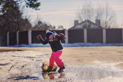 Child girl in waterproof pants jumping in puddle on winter walk Stock Photos