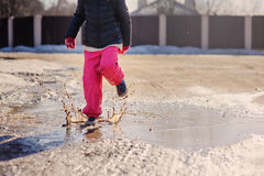 Child girl in waterproof pants jumping in puddle on winter walk Stock Images