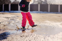 Child girl in waterproof pants jumping in puddle on winter walk Royalty Free Stock Image